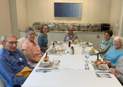 Picture of new Lasell Village residents dining with President Anne Doyle.